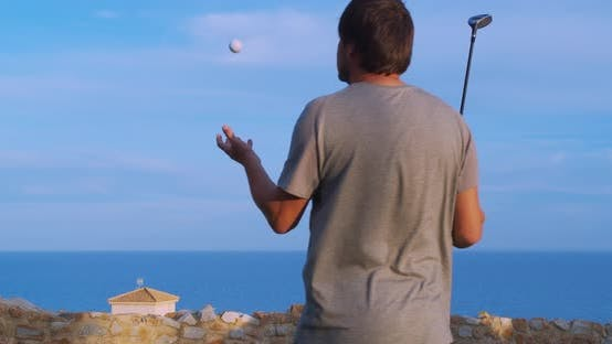 Thumbnail for Caucasian Golf Player Holding a Club Looking Into the Distance Behind a Flying Ball, Golf Field