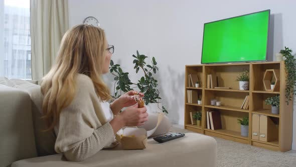 Thumbnail for Woman Eating and Watching TV with Green Screen