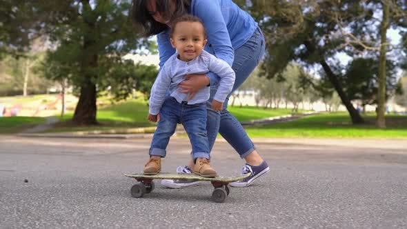 Thumbnail for Little Boy Standing on Skateboard, Rolling with Help of Mother