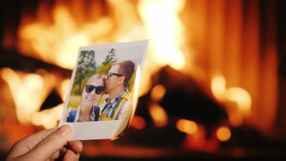 A Man Burns a Photo of a Couple in Love and Throws It Into the Fireplace
