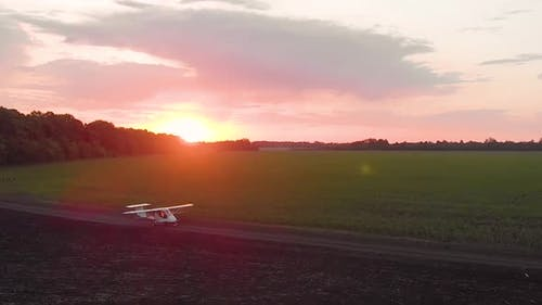 A Small Airplane Takes Off From a Field at Sunrise.