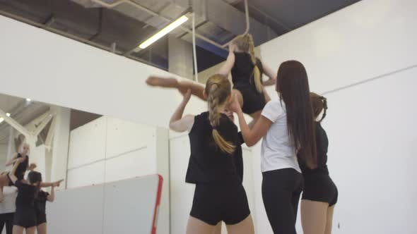 Thumbnail for Coach Helping Girls Learning Cheerleading Stunt
