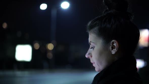 Nachdenkliche einsame Frau wartet auf jemanden in der Stadt Nacht sitzt auf einer Bank
