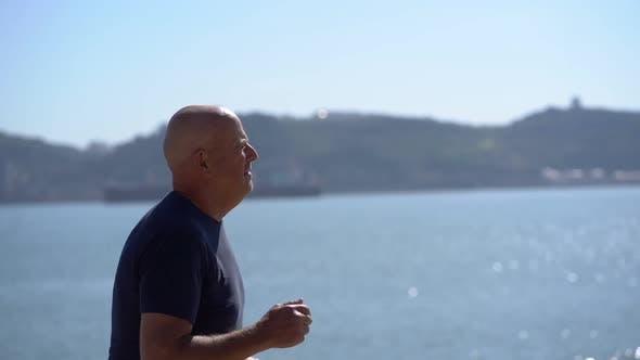 Thumbnail for Focused Mature Man Running at Riverside
