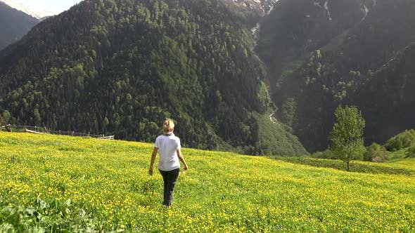 Thumbnail for Blond Haired Woman Walks Alone in Meadow With Yellow Flowers in Forest