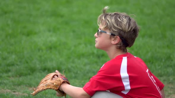 Thumbnail for A boy spits out sunflower seed shells on a little league baseball field.