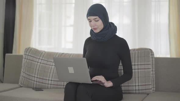 Cover Image for Young Muslim Woman Was Working or Chatting By Laptop and After Somebody Called Her By the Smartphone