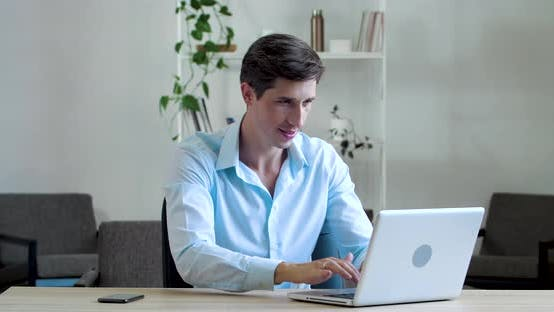 Thumbnail for Attractive Caucasian Man Sitting with Laptop Typing Smiles at Camera Showing Hand OK Sign