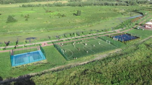 Mini football and basketball fields. People playing games on sports fields at sunny summer day