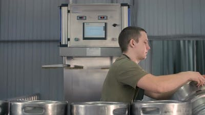 A Male Brewer Washes and Sterilizes Beer Kegs Using an Automatic Beer Keg Sterilization Machine