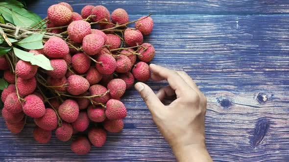 Hand Pick Lychee on a Wooden Background Top Down