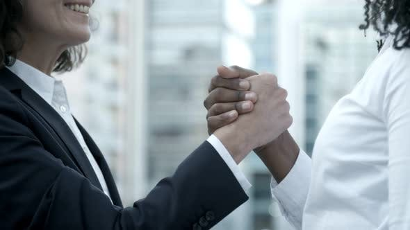 Smiling Caucasian Woman Shaking Hands with Colleague