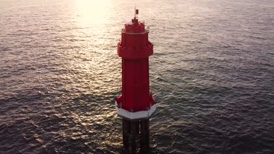 Red Lighthouse in the Ocean on Sunset