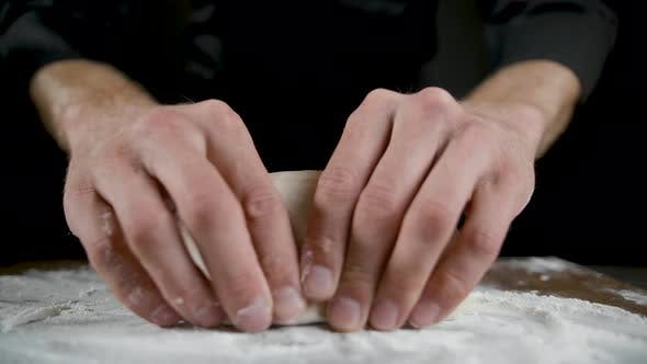 Cook Breaks the Dough in the Hands in the Dark Kitchen