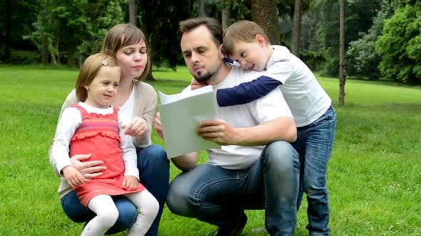 Thumbnail for Family, Middle Couple in Love, Cute Girl and Small Boy, Read Document in the Park