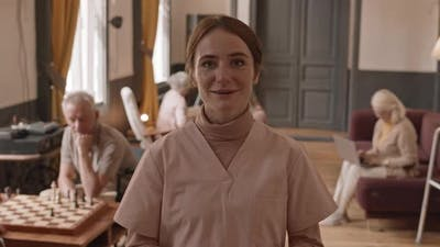Cheerful Nurse Talking on Camera in Nursing Home