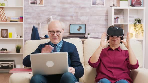 Thumbnail for Elderly Age Woman Sitting on Sofa Wearing Virtual Reality Goggles
