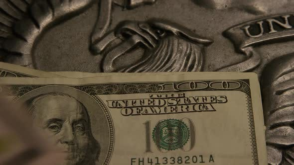 Thumbnail for Rotating footage shot of American paper currency on an American eagle shield background
