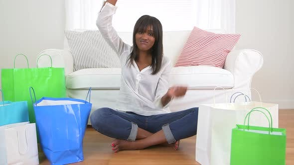 Thumbnail for Happy excited black woman cheering with her shopping bags