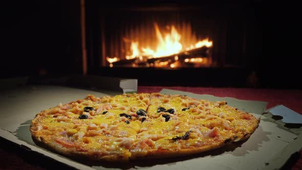 Cover Image for Pizza in a Cardboard Box on the Table Against the Background of the Fireplace