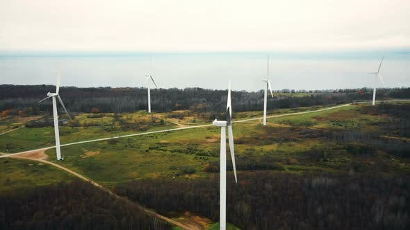 Thumbnail for Beautiful Aerial Panorama of Windmill Turbine Farm Standing Still in Autumn Forest Lake Field