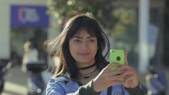 Cover Image for Smiling Young Woman Taking Pictures with Smartphone Outdoor