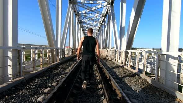 Male Athlete Walking on Rails. Back View Tracking Shot of Unrecognizable Sportsman Walking Along