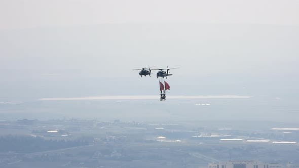 People Hanging From Helicopter Performing Stunt Flying