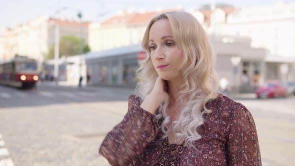 A Middleaged Caucasian Woman Feels Sick and Has a Headache in an Urban Area