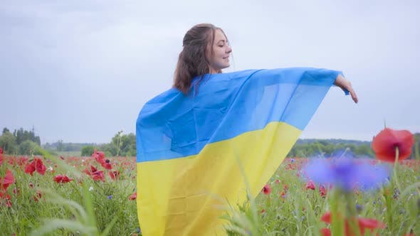 Thumbnail for Pretty Girl Standing in a Poppy Field Covered with Flag of Ukraine. Connection with Nature