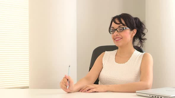 Thumbnail for Young Hispanic business woman sitting at a desk talking