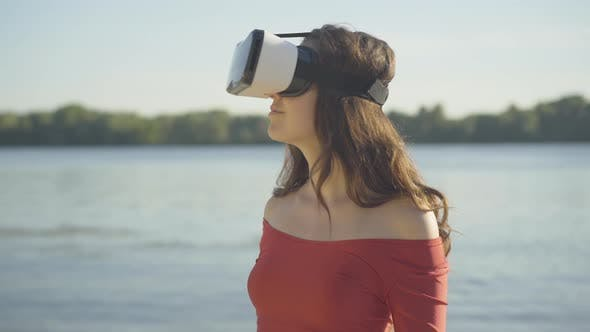 Portrait of Young Brunette Woman in VR-glasses Looking Around with Excited Surprised Facial
