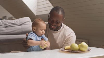 Baby Trying Eating Apple with Parents