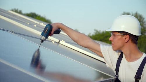 Young Enginneer Installing New Sunny Batteries. Worker in a Uniform and Hardhat Installing