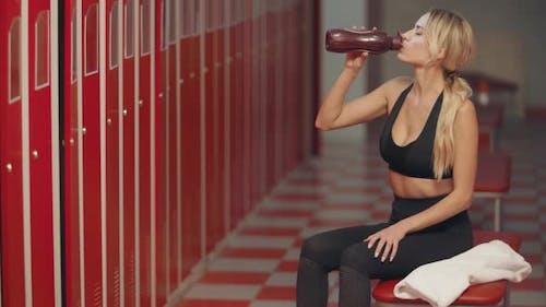 Tired Sportswoman Drinking Water in Dressing Room