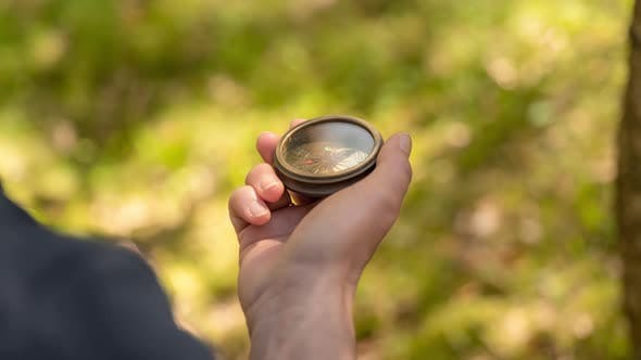 Traveler Hand Holds a Compass in Forest