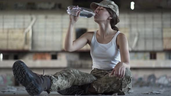Cover Image for Attractive Young Woman in Military Uniform Drinking Water From the Bottle Sitting on the Floor