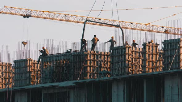 Thumbnail for Building Construction. A Crane on a Construction Site Lifts a Load. Workers at a Construction Site