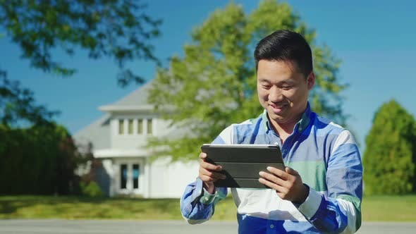 Cover Image for A Cheerful Chinese Man Uses a Tablet Near His Home