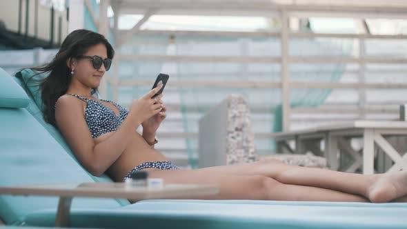 Thumbnail for Slender Brunette Girl Lying on a Sunbed and Surfing the Net on Her Phone in Summer