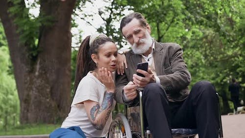 Granddaughter with Dreadlocks and Respected Bearded Retired Granddad in Wheelchair Using Smartphone