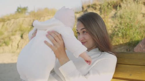 Happy Mom tient petit bébé dans ses bras et sourires