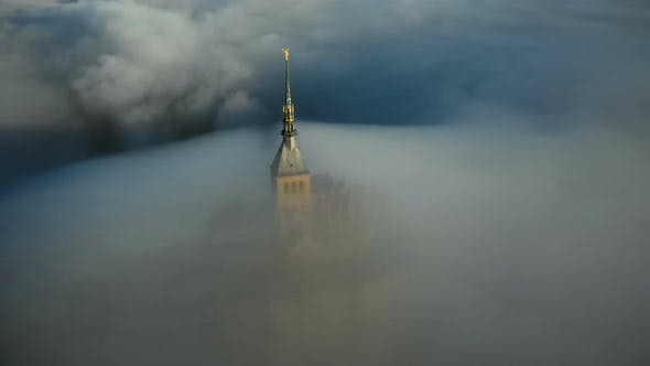 Cover Image for Drone Flying Above Sunrise Mont Saint Michel Castle Steeple Covered By Thick Fog Clouds Flowing Into