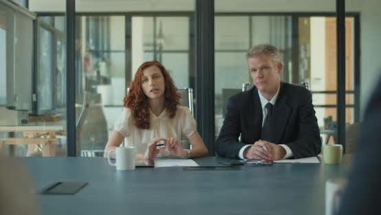 Thumbnail for Zwei Geschäftsleute sprechen mit ihren Kollegen im Büro über Projektstrategien im Meetingraum.