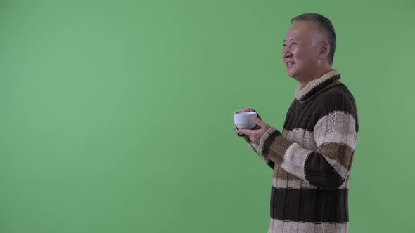 Thumbnail for Profile View of Happy Mature Japanese Man Drinking Coffee Ready for Winter