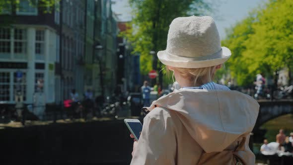Thumbnail for A Woman with a Smartphone in Her Hands and Headphones Is Standing Near a Canal