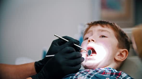 Thumbnail for A Little Stressful Boy with Baby Teeth Having a Treatment in the Dentistry