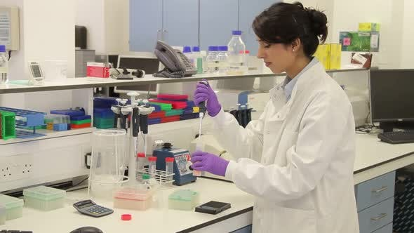 Thumbnail for Scientist dropping liquid with pipet into vial in genetic laboratory