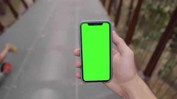 iPhone 11 green mock-up blank screen. walking outdoors in the urban park street.