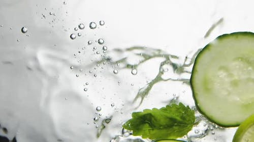 Person Throws Cucumber Lime and Mint Leaves Into Water